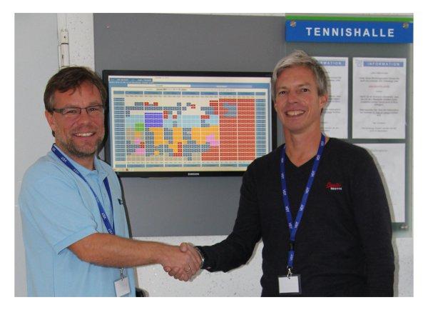 Gerald Brandstätter von tennis04 und Andre Jethon vom Lintorfer Tennisclub schütteln sich die Hände vor dem Bildschirm des Online-Buchungssystems von tennis04